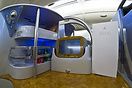One side of the businessclass booth with a menu chart, personal mini-b...