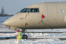 A snowman has been made by the airport staff in front of a parked CRJ ...