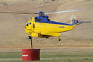 This Sikorsky S-61 is filling up the tank with fire retardant liquid r...