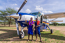 Local Kenyan tribesman in front of a Grand Caravan used for flying in ...