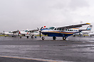 Line-up of several Cessna Grand Caravans on the apron during heavy rai...