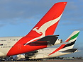 Qantas and Emirates A380 A6-EEI parked up on remote stands.