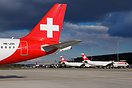 Tail of Holiday Jet A319 HB-JOH and 2 Swiss A340-300 parked in the bac...