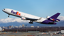 A Fedex MD-11 departs Anchorage with the city as a backdrop.