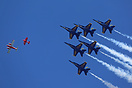 The Blue Angels in formation behind Sean D Tucker's Pitts Special over...