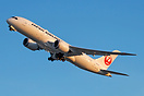 JAL's 787-8 lit in the golden light as it departs on its delivery flig...