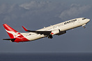 With the Coral Sea behind a qantas 737-800 departs Cairns for Brisbane...