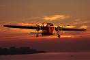 Bristol Freighter on final approach against a colourful sunset sky. Co...