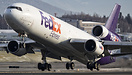 A Fedex MD-11 rotates away from runway 33 at Anchorage in a shower of ...