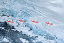 Swiss demo team Patrouille Suisse passing in front of a glacier on the...